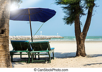 Wooden chair on the beach with sunlight