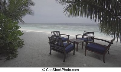 Wooden Chairs and Table in the Sand at Maldives Resort