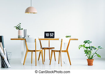 Wooden chairs at desk with laptop in white home office interior with plant and lamp. Real photo