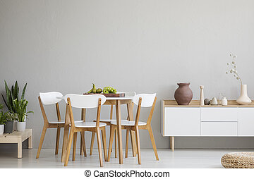 Wooden chairs at table in grey dining room interior with plants and white cupboard. Real photo