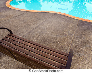 Wooden chairs on a concrete floor. Beside the pool