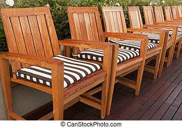 Wooden Chairs On Deck - A line of teak wood chairs with...