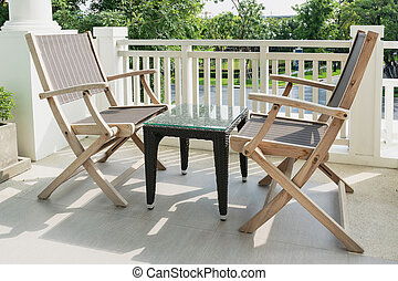 wooden chairs on modern balcony overlooking a garden