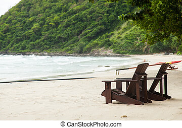 Wooden chairs on the beach.