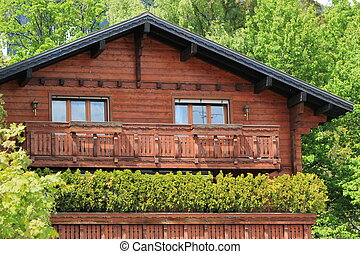 Wooden chalet among summer trees