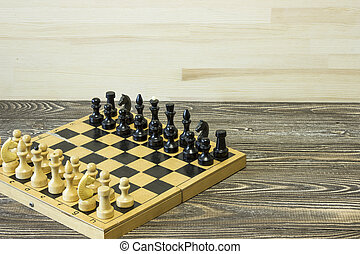 Wooden chess board with figures on the table