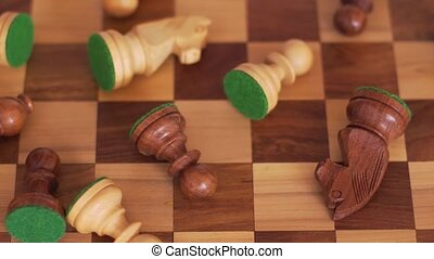 Wooden chess pieces are in a mess on a chessboard. Camera movement from right to left.