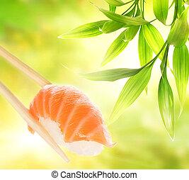 Wooden chopsticks holding salmon sashimi