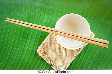 Wooden chopsticks kitchenware set on bowl and banana leaf background