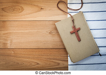 wooden Christian cross necklace on holy Bible on wood table