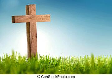 Wooden christian cross on green grass