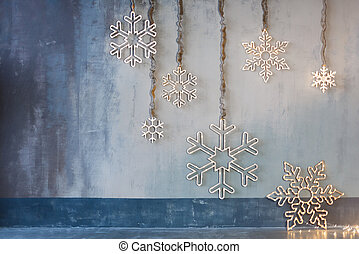 Wooden christmas decoration for the walls. Glowing snowflakes with garland lights on gray concrete background. Christmas background, winter holidays theme.
