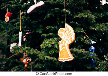 Wooden Christmas toy in the shape of an angel on the branches of a Christmas tree.