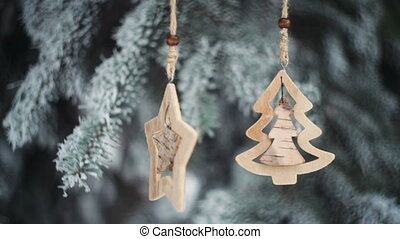 wooden Christmas toys on snowy fir branch in winter park