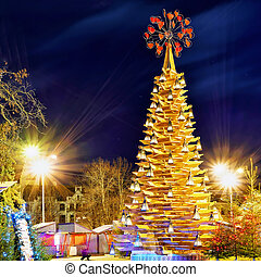Wooden Christmas tree and the market at night in Riga -...