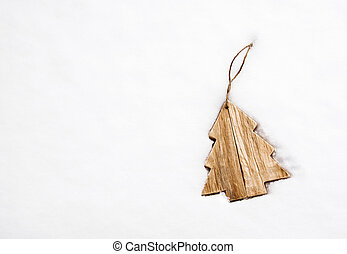 Wooden Christmas tree decoration on white snow