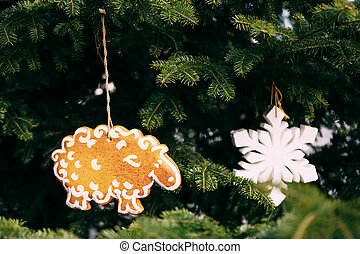Wooden Christmas tree toy in the shape of a lamb and a white snowflake on fir branches.