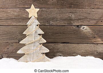 Wooden Christmas tree with twine garland in snow