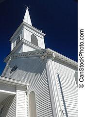 wooden church spire against deep blue sky, vertical