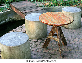 wooden circular table and cement chairs in a park