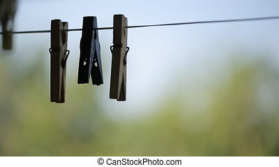 Wooden clothespins hang on clothesline outside in daytime....