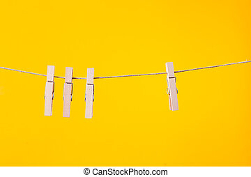 Wooden clothespins hanging on a clothesline rope