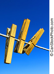 wooden clothespins on clothesline against blue sky
