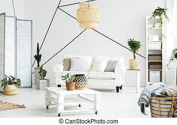 Wooden white coffee table and comfortable sofa in lounge