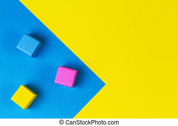 Wooden colorful blocks on geometric yellow and blue background. Top view, flat lay