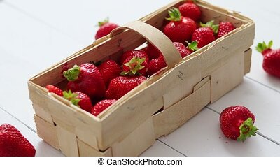 Wooden container with fresh red strawberries. Placed on ...