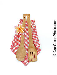 Wooden cooking utensils with checkered cloth isolated on white