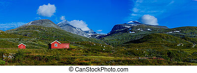 Red wooden cottage in the valley. Stone snowy mountains. Norway. Panorama
