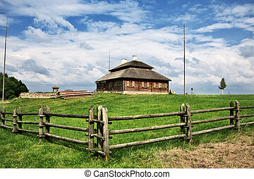 wooden cottage on green hill under cloudy sky