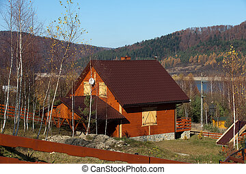 wooden cottage on the lake in an autumn landscape