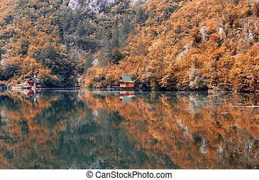 wooden cottages on river landscape autmn season
