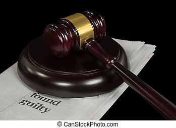 wooden court gavel on newspaper