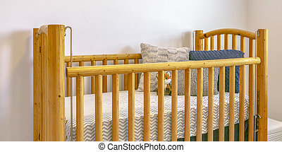 Wooden crib with mattress pillows and stuffed toy