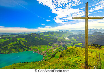 Wooden cross along a trail around the summit of Mount Rigi Kulm the highest peak on Mount Rigi over 13 lakes and peaks of Swiss Alps. Canton of Schwyz and Lucerne, Central Switzerland.