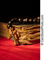 Wooden cross crucifix on the old closed holy bible.