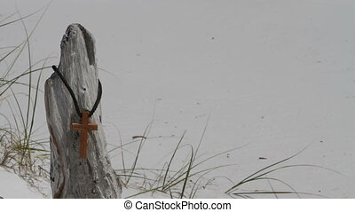 Wooden Cross Hanging On Driftwood - Wooden cross hangs by a...