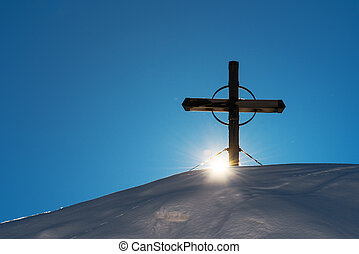 Wooden cross on snow capped mountain hill