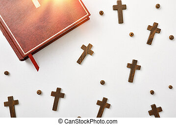 Wooden crosses round beads and bible on wooden table top
