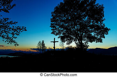wooden crosses sit upon a hill in the sunset with tree and lake