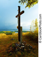 wooden crosses sit upon a hill in the sunset with tree and lake.