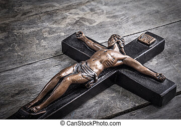 Crucifix on old wooden tablel, retro close up