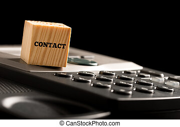 Wooden cube with the word Contact on a phone