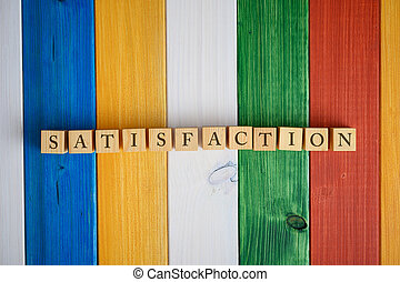 Wooden cubes in a row spelling the word Satisfaction