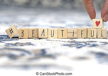 Wooden cubes with a hashtag and the word beautiful, social media concept background