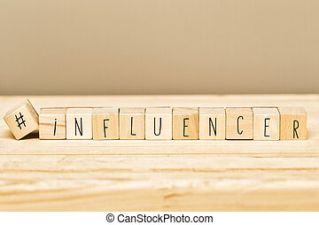 Wooden cubes with a hashtag and the word Influencer, social media concept and background