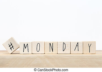 Wooden cubes with a hashtag and the word Monday, social media concept near white background
